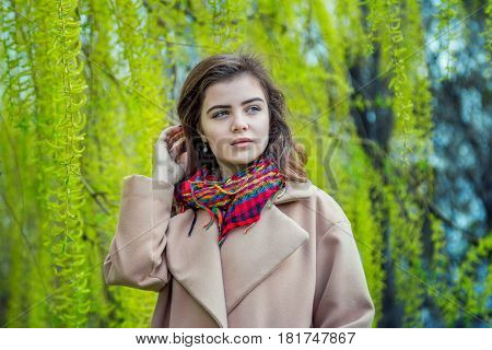 Portrait of beautiful teen girl, wearing trendy oversize beige coat and colorful scarf, standing near weeping willow tree, springtime outdoors.