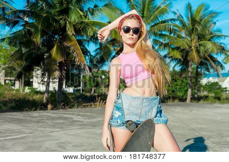 Beautiful and fashion young woman posing with a skateboard near palms. Healthy lifestyle. Extreme sports. Caucasian model with blonde long hair.