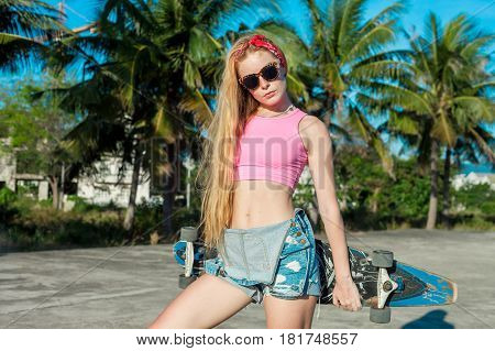 Skater girl posing with a skateboard near palms on the beach. Female in colourful clothers. Extreme sports. Caucasian model with blonde long hair.