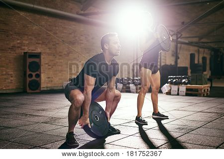 Man And Woman Lifting Weight Discs From