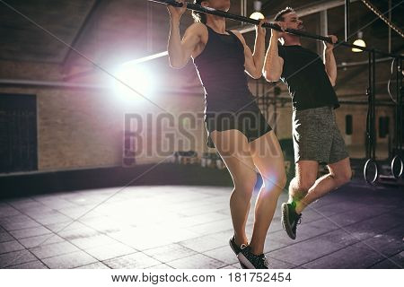 Two Sportive People In Sportswear Doing Pull-ups