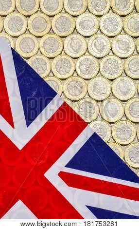 British Union Jack flag and currency - bimetallic one pound coins introduced in March 2017. Overhead point of view. Vertical.