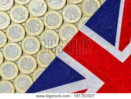 British money - new bimetallic one pound coins introduced in March 2017 and Union Jack flag. Overhead point of view.