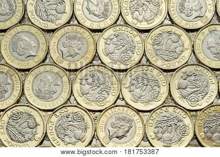 Close up of British money new pound coins background laid flat. Overhead point of view. The bimetallic coin was introduced in March 2017. These coins are dated 2016.