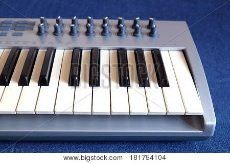 Electronic synthesizer keyboard with many control knobs on denim background front view closeup