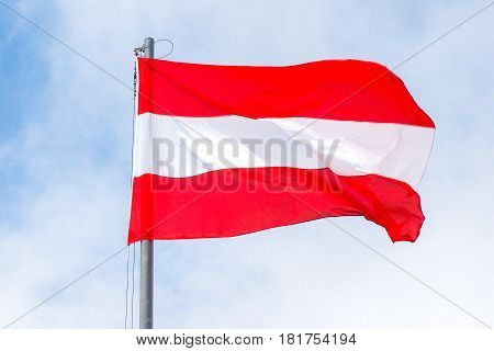 Flag of Austria waving in sunny and cloudy sky