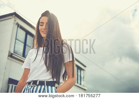 Woman Wearing Striped Pants Puts Hand In Pocket