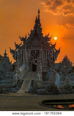 Beautiful ornate white temple located in Chiang Rai northern Thailand. Wat Rong Khun (White Temple), is a contemporary unconventional Buddhist temple in sunset on april 27 2016