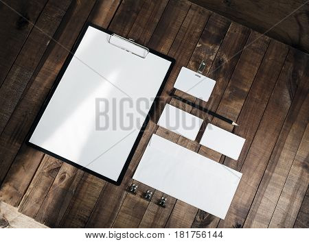 Photo of blank stationery set on wood background. Corporate identity template. Blank letterhead business cards envelope badge and pencil. Responsive design mock up. Top view.