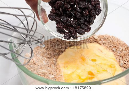 Wheat bran muffins preparation : Adding raisins to the mix to prepare integral wheat bran muffins