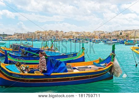 Fishermen On Luzzu Colorful Boat At Marsaxlokk Harbor In Malta