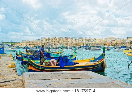 Fishermen On Luzzu Colorful Boat At Marsaxlokk Harbor Malta