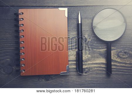 notebookpen and reading glass on wooden table