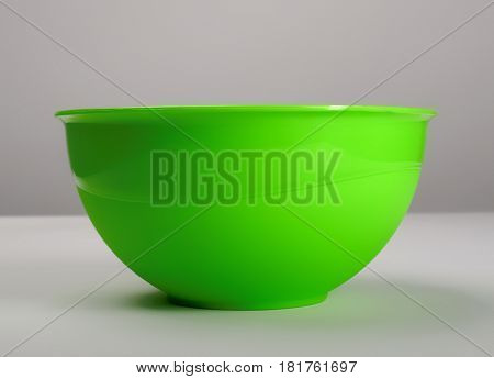 Green plastic deep dish  on the table, front view