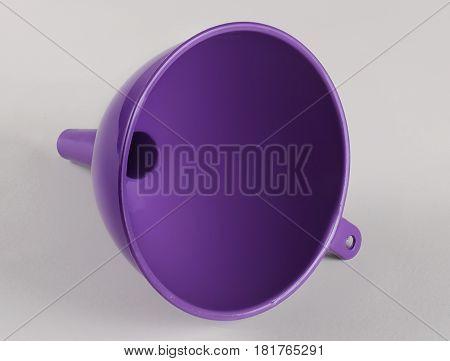 Purple plastic kitchen funnel liquid on gray background