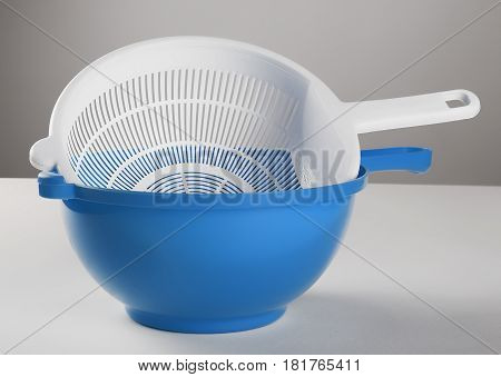 White plastic colander in blue bowl isolated on white background