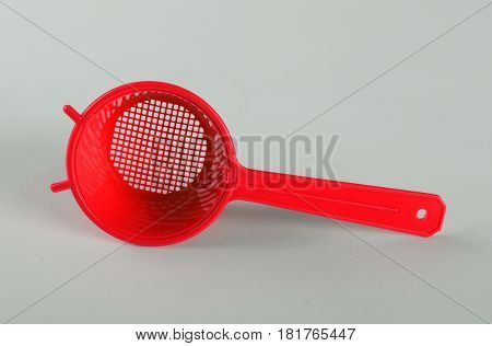 Red plastic tea strainer isolated on white background