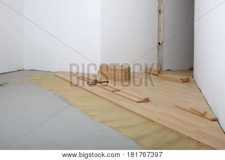 Construction in a renovated room installation of parquet. Pad applied with glue for parquet