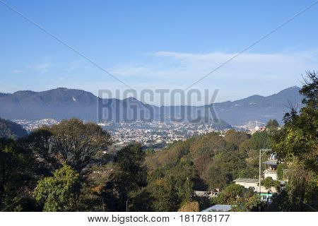 Wide angle morning view of scenic southern valley of San Cristobal de las Casas displaying urban sprawl beyond dense trees under clear blue sky