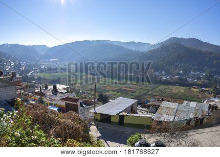 Plots of farmland in valley of San Nicolas bordered by small housing communities in San Cristobal de las Casas Chiapas on sunny morning