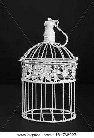 White metal bird cage on black background front view