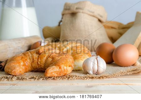 Close up shot of who garlic on hemp sackcloth with bread and bakery background