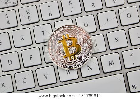 One Silver Bitcoin Coin On The Keyboard