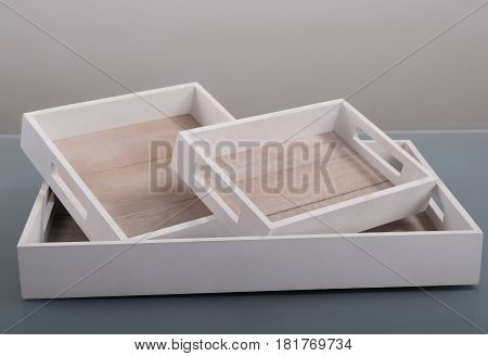 Three white wooden trays on gray background