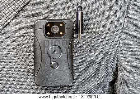 black plastic body camera or DVR is fixed by the clip on pocket plaid jacket and metal ball pen