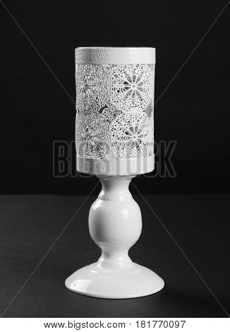 White vintage table candlestick front view on black background