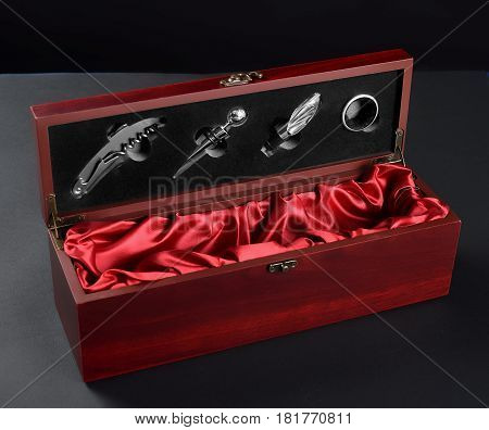 Set of a vine opener in a wooden case with bottle of red vine. Isolated on white.