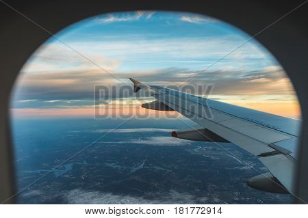 Sunset aerial view through airplane window over wing. Flying at sunset and looking out of the window and enjoying the panoramic view. Travel and transportation concepts