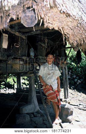 BANAUE, IFUGAO / PHILIPPINES - CIRCA 1990: An Ifugao woman poses for a photograph outside of her home near Banaue.