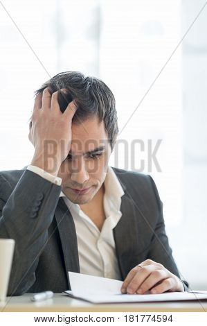 Businessman Working At Office Desk Reading A Report Or Document