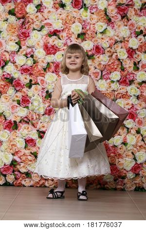 Portrait of a beautiful blonde little girl in white gown with purchases in hands, background of a flower wall in the studio