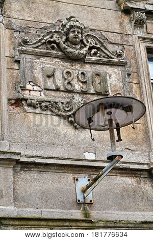 Destroyed lamp on the decayed facade of a house in Magdeburg