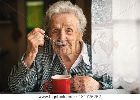 Mature woman drinking tea in the kitchen.