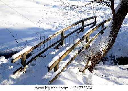 old wooden bridge on a winter mountain stream