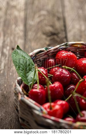 Fresh cherries in wicker basket on the wooden background