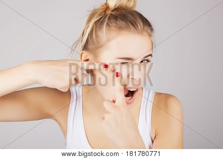 funny blond girl pressing out blemishes from her face