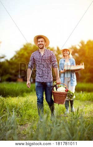 Satisfied farmers couple returning from garden with vegetables
