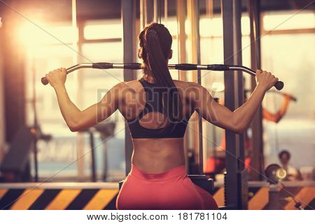 Woman doing exercise for chest and back muscles on machine, back view