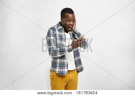 Close Up Portrait Of Black Shocked Hipster In Stylish And Trendy Yellow Pants, Holding Smartphone In