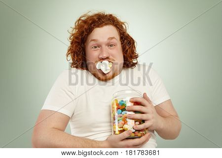 Never Enough. Close Up Shot Of Funny Young Plump Man With Curly Ginger Hair Holding Tight Jar Of Can