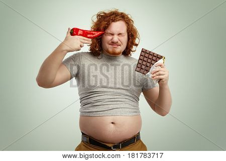 Red-haired Young European Bearded Man Wearing Shrunk T-shirt With His Stomach Sticking Out Of Jeans,