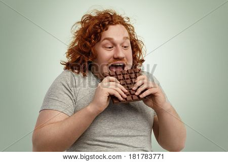 Happy Excited Young Chubby Red-haired Male Opening Mouth Widely While Biting Bar Of Chocolate, Feeli