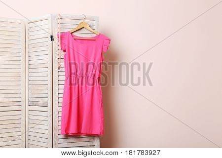 Pink Dress Hanging On Folding Screen On A Beige Background