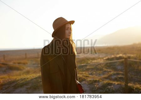 Peaceful Young Female Wearing Sylish Hat, Coat And Shoulder Bag Having Joyful Carefree Look While Re
