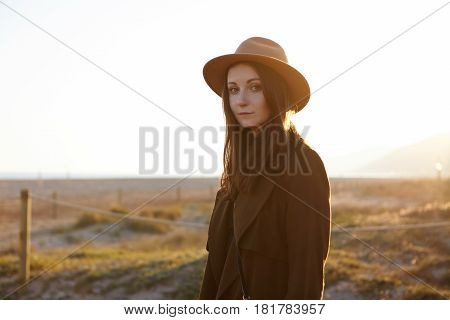 Outdoor Portrait Of Beautifulcaucasian Girl Wearing Fashionable Coat And Hat Feeling Carefree And Pe
