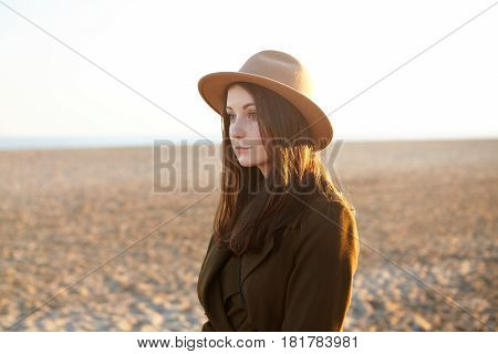 Attractive Young European Female Dressed In Stylish Overclothes Having Nice Walk Along Coastline On